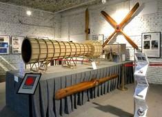 Seitenansicht eines langen Holzrohrs auf einem Ausstellungstisch, Bauteil eines historischen Fluggeräts.