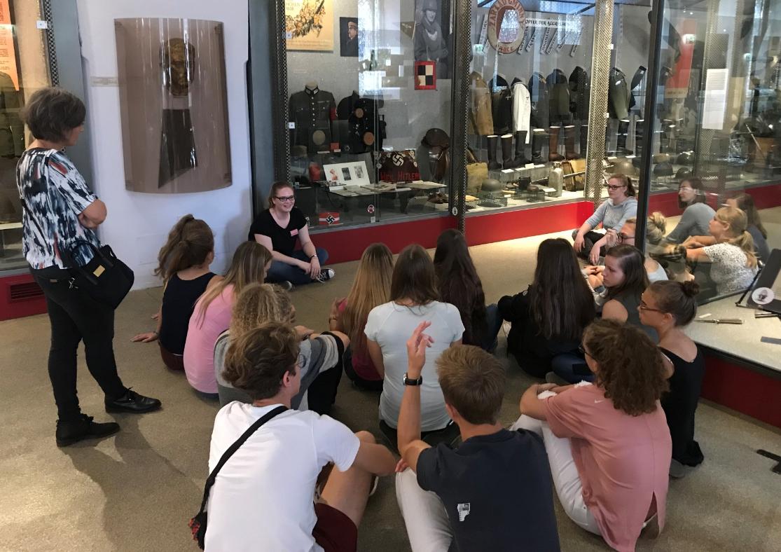 Kulturvermittlerin Mag. Katharina Kraus sitzt mit einer kleinen Gruppe Jugendlicher am Boden zwischen Vitrinen.