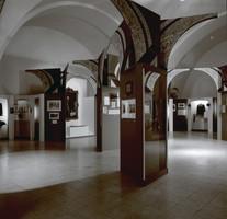Vitrinen an den Seiten von Torbögen im Ausstellungssaal.