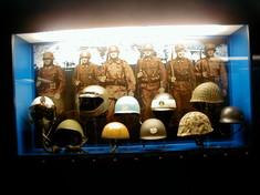 Vitrine mit verschiedenen Soldatenhelmen.