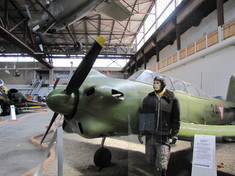 Schaufensterpuppe in Pilotenuniform neben einem Militärflugzeug im Hangar.