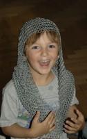 Lachendes Kind mit einem Kettenhemd über Kopf und Schultern.