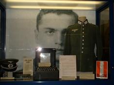 Vitrine mit Uniform, Kappe und Dokumenten.