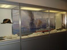 Vitrine mit Gemälde eines brennenden Schiffes, daneben eine Kapitänsmütze.