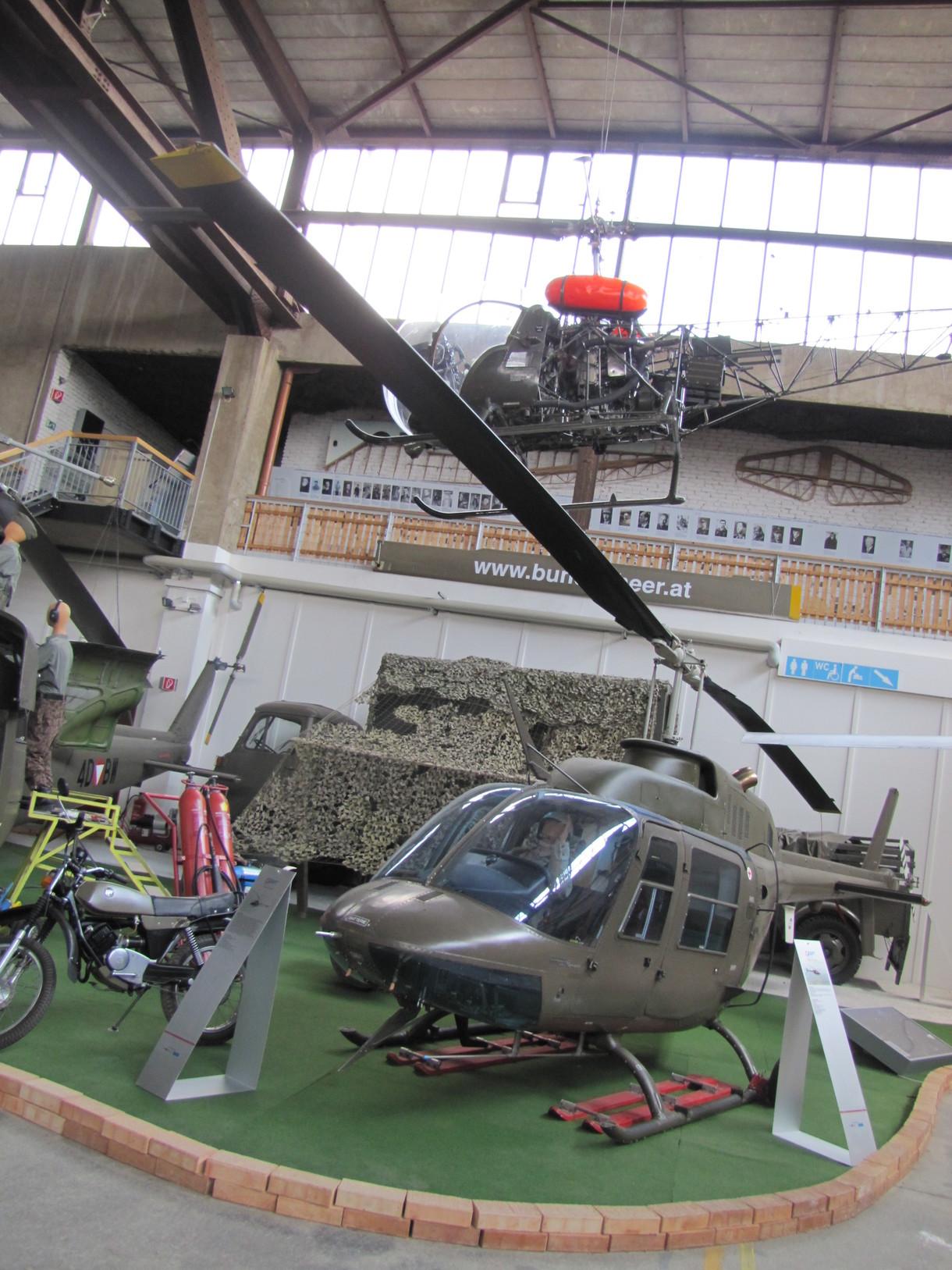 Hubschrauber am Boden auf einem Grasteppich, darüber ein weiterer Hubschrauber von der Decke hängend.