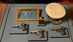 Drei Pistolen, eine Granate, ein Hut und eine Scheibe mit Einschussloch in der Vitrine.