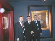 Drei Männer im Anzug stehen vor einem Gemälde.