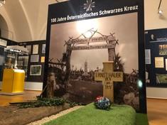 Nachgestelltes Grab mit Holzkreuz und Grasteppich im Ausstellungsraum.