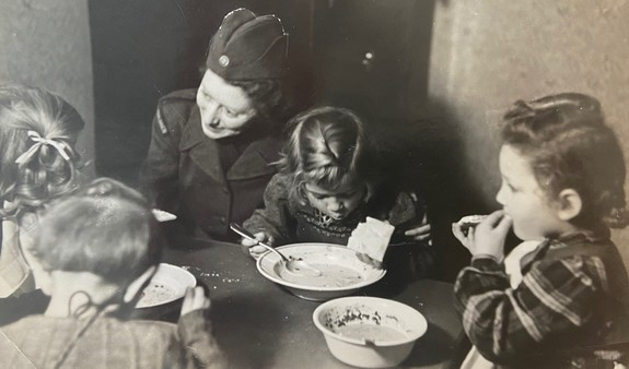 Schwarz-Weiß-Foto einer Mitarbeiterin der schwedischen Hilfsorganisation Rädda Barnen (Rettet die Kinder) und vier Kindern beim Essen.
