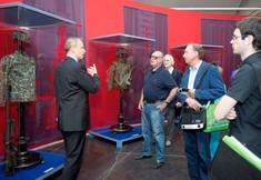 Kurator steht vor Besuchergruppe und zeigt auf Vitrinen mit Uniformen.