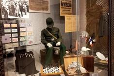 Schaufensterpuppe in Uniform umgeben von einem Koffer mit Kleidung, einem Schachspiel. Zeitungsausschnitten und Flaggen.