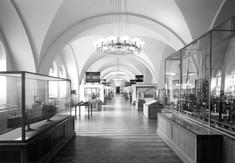 Ausstellungsraum mit Vitrinen links und rechts, an der Decke ein Luster.