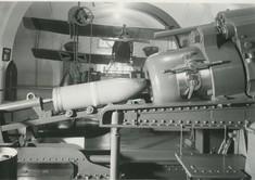 Schwarz-weiß-Foto der Ladevorrichtung eines GEschützes, im Hintergrund ein Militärflugzeug an der Decke aufgehängt.