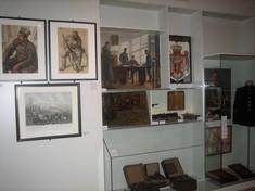 Bilder an der Wand, aufgeklappte Schatullen in einer Vitrine davor.