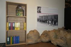 Bücherregal mit einigen Ordnern und einem Spielhaus, daneben große zugebundene Säcke. Darüber hängt eine Foto- und Texttafel.