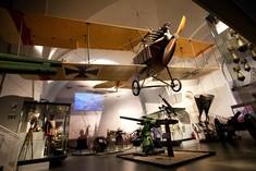 Kampfflugzeug hängt von der Decke, darunter Haubitzen, Kanonen und Vitrinen mit Uniformen.
