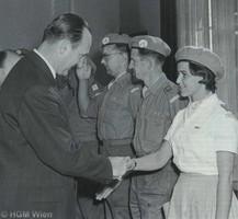 Schwarz-Weiß-Foto von Mann im Anzug, der einer Soldatin die Hand schüttelt, neben ihr stehen weitere Soldaten.
