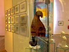 Jakobinermütze in einer Vitrine, dahinter an der Wand gerahmte Fotografien.