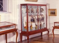 Biedermeier-Vitrine mit vier Gala-Uniformen aus der Kaiserzeit.