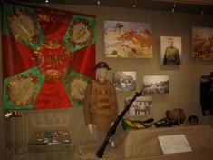 Vitrine mit Uniform, Gewehr, Flaggen und Fotos.