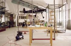 Aufbau einer Ausstellung mit Arbeitsbänken aus Holz im Ausstellungsraum, verschiedenen Werkzeugen und einem an der Decke hängenden Flugzeug.