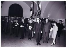 Besucher in dunklen Anzügen und eine Frau im hellen Kleid betrachten die Ausstellung.