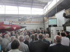Besuchermenge in einem Hangar, in dem Flugzeuge am Boden stehen und von der Decke hängen.