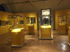 Ausstellungsraum mit beleuchteten Vitrinen.