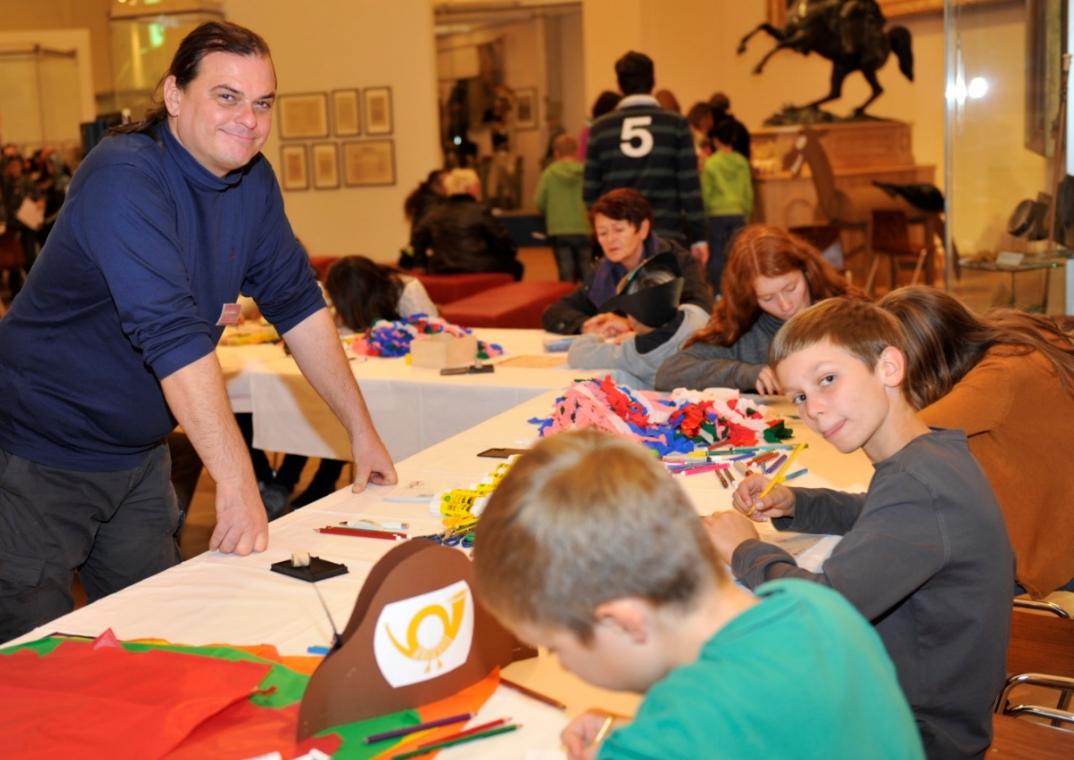 Kulturvermittler Erich Stadlbauer steht lächelnd vor Tischen, an denen Kinder mit Papier und Stiften basteln.