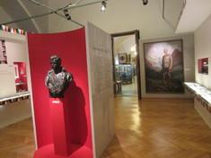 Ausstellung mit Büste, Gemälde und Info-Text an der linken Wand.