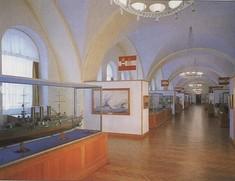 Vitrine mit einem Schiffsmodell, dahinter eine Schauwand mit Gemälde und Österreich-Flagge.