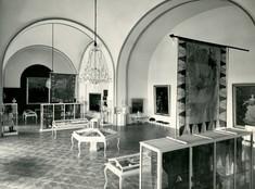 Schwarz-weiß-Foto mit Schaukästen und Vitrinen im Raum verteilt, an der Decke Kronleuchter, an der Wand eine Flagge.