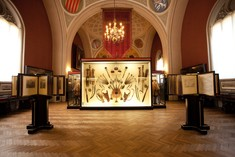Ausstellungsraum mit verschiedenen Waffen in einer beleuchteten Vitrine. Rechts und Links sind Bilder, historische Landkarten und Briefe aufgestellt.