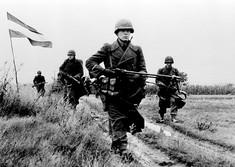 Schwarz-Weiß-Foto von Soldaten, die bewaffnet über ein Feld gehen, daneben weht die österreichische Fahne.