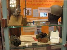 Vitrine mit Helm, Dokumenten und Kleingeräten.