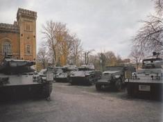 Mehrere Panzer stehen vor dem Museum im Garten.