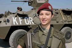 UNO-Soldatin lächelt vor einem Panzer.