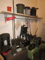 Tisch mit Rucksack und Funkgeräten, darüber an der Wand ein Holzbrett mit verschiedenen Spulen.