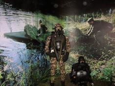 Anzug des Jagdkommandos vor einer Fotowand, auf der Soldaten am Seeufer in ein Boot steigen.