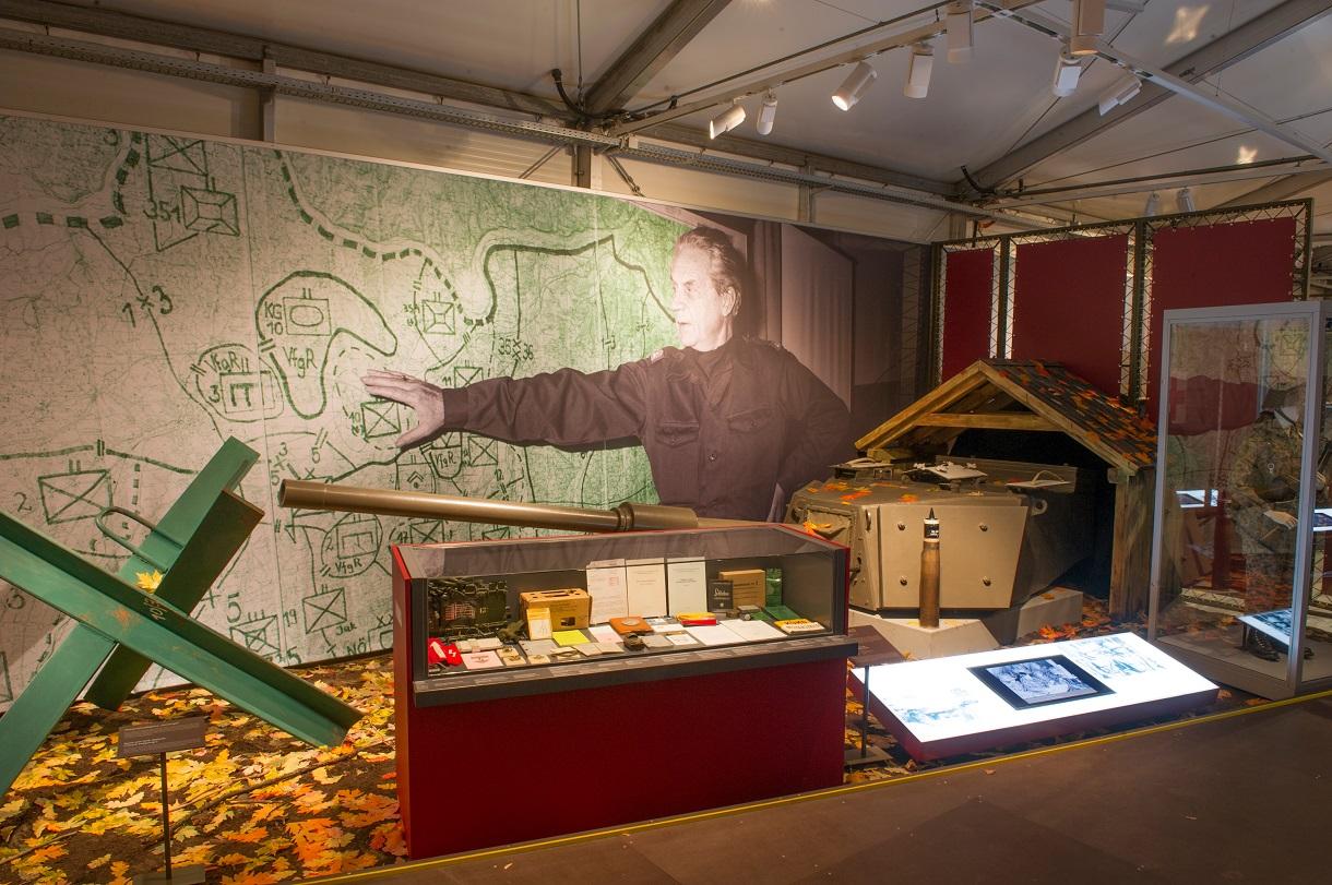Bauteile und ein kleines Holzhaus, davor ein Schaukasten mit zahlreichen Dokumenten und an der Rückwand eine Landkarte mit verschiedenen Markierungen, auf die ein Soldat zeigt.