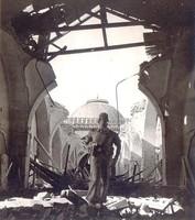 Soldat mitten in Trümmern eines zerstörten Gebäudes.