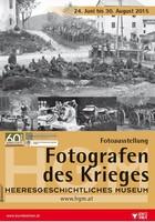 """Ausstellungsplakat """"Fotografen des Krieges"""" mit einer Fernaufnahme von Soldaten, die am Bauch liegend eine Lichtung beobachten."""