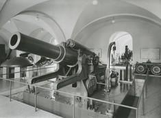 Schwarz-weiß-Foto einer Haubitze auf einem Podest umgeben von Glas-Absperrung.