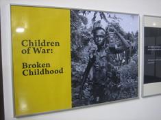 """Schwarz-Weiß-Foto eines schwer bewaffneten Kindes im Dschungel, daneben der Text auf gelbem Hintergrund """"Children of War: Broken Childhood"""""""