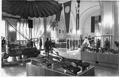 Schwarz-weiß-Foto von Schaukästen mit Gewehren und anderen Kriegsobjekten.