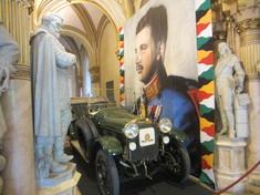 Oldtimer mit offenem Verdeck in der Feldherrenhalle des Museums vor einem Wandteppich mit dem Porträt von Kaiser Karl I.