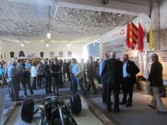 Besuchermenge in einem Ausstellungssaal, im Vordergrund ein Rennwagen.