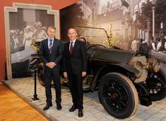 Zwei Männer im Anzug stehen vor einem Oldtimer mit offenem Verdeck im Ausstellungsraum.