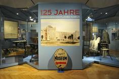 Infotafel mit Ausstellungstitel und Zeichnung der Museumsfassade.