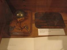 Kleine Weltkugel auf einem Holzbrett mit Anker verziert in einer Vitrine.